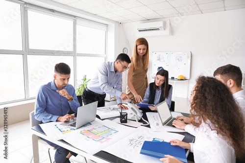 Architect teaching young people in office Canvas Print