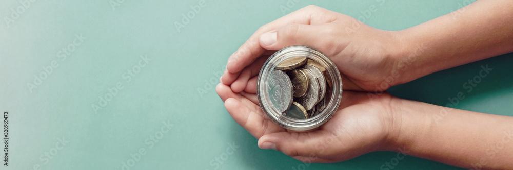 Fototapeta child hands holding money jar,  donation, saving, charity, family finance plan concept, Coronavirus economic stimulus rescue package, superannuation, financial crisis concept