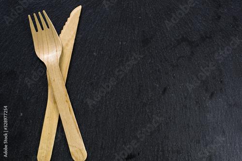 Obraz na plátne cubiertos de madera, chuchillo y tenedor ecologicos con fondo oscuro