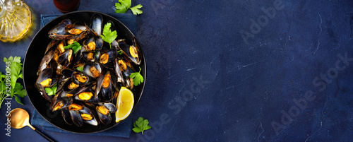 Valokuva A plate with steamed mussels on dark blue background