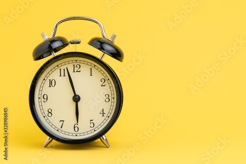 Alarm clock at almost 6 o'clock in the morning on yellow background with copy sp Fototapeta