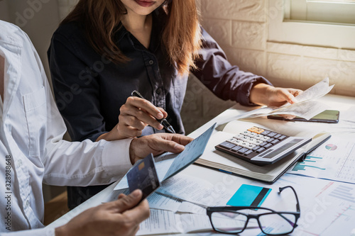 Fototapeta Stressed young couple checking bills, taxes, bank account balance and calculating expenses in the living room at home obraz