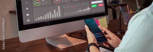 Fototapeta Stock exchange market concept, businesswoman trader looking on smartphone and computer with graphs analysis candle line on table in office, diagrams on screen. proportion of the banner for ads. obraz