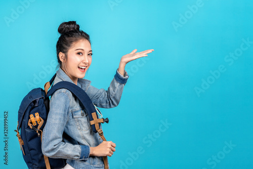 Fototapeta Happy asian woman travel backpacker standing hand open to copyspace on blue background. Cute asia girl smiling wearing casual jeans shirt and finger pointing to aside for present promotions. obraz