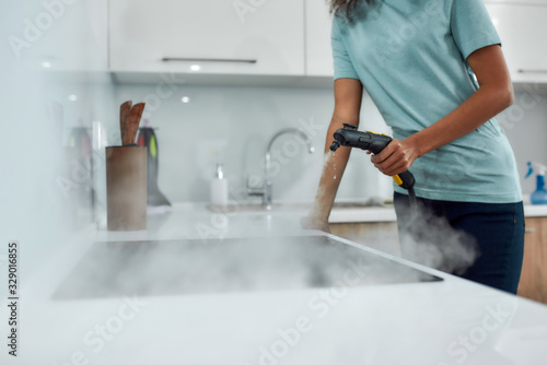 Obraz Service at work. Cropped view of a woman in uniform cleaning electric stove with steam cleaner while working in the modern kitchen - fototapety do salonu