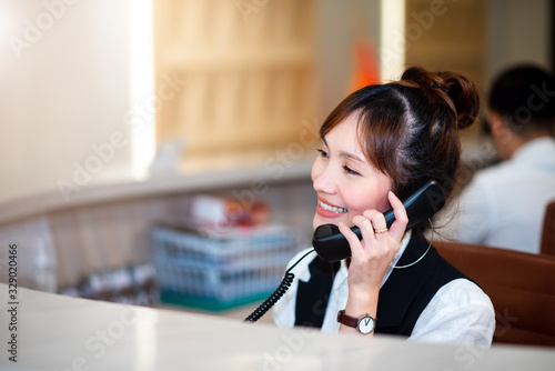 Smart Professional Asian Woman Smiling Face in Operator , Call Center Department. She is Use Telephone Working with Happy Service Mind Telecommunication Department