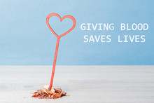 """A Red Heart Carved From Wood On A Blue Background Stands On The Table. Lettering On The Background: """"Giving Blood Saves Lives""""."""
