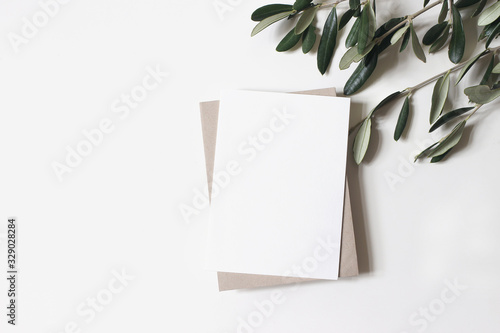 Summer wedding stationery mock-up scene. Blank vertical greeting card, craft paper envelope and olive branches isolated on white table background. Feminine Mediterranean flat lay, top view. - 329028284