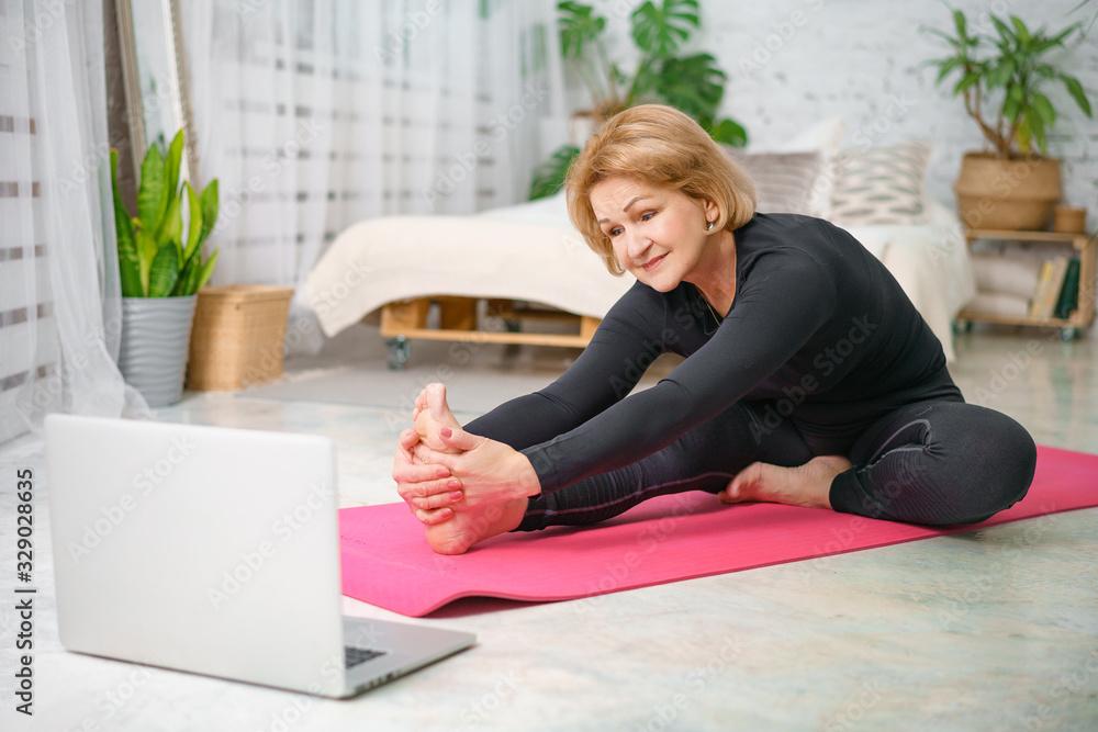 Fototapeta Fitness training online, senior woman at home with laptop