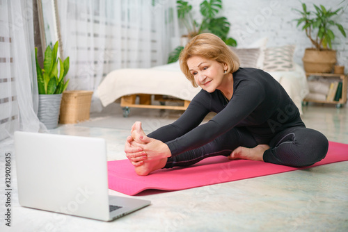 Fitness training online, senior woman at home with laptop - 329028635