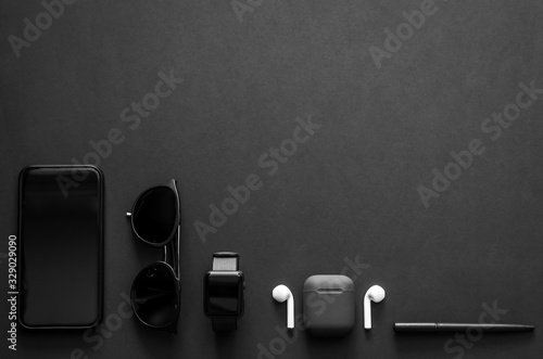 Obraz Men gadgets in modern lifestyle on dark background for minimalist flat lay black concept.. - fototapety do salonu