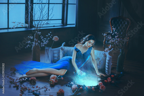 Photo Fantasy young sorceress woman in long blue dress touch divine old mirror