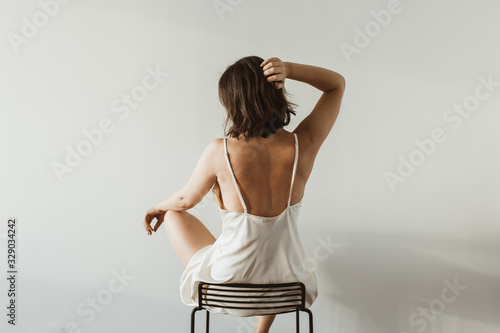 Obraz Young pretty woman in silk underwear sitting on black stool on white background. Fashion concept. - fototapety do salonu