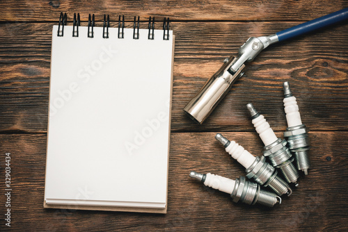 Obraz Spark plugs and blank page notepad with copy space on brown wooden workbench background. - fototapety do salonu