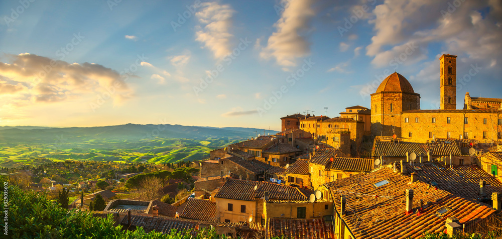 Fototapeta Tuscany, Volterra town skyline, church and panoramic view at sunset. Italy
