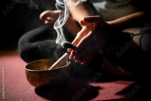 Photo Young woman sitting in yoga pose and holding smoldering stick in her hands