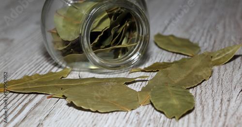 Fototapeta liście laurowe leżą na drewnianym stole, obok otwarty słoiczek z tą przyprawą w