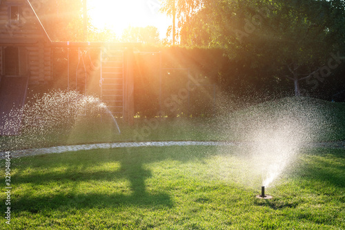 Obraz Landscape automatic garden watering system with different sprinklers installed under turf. Landscape design with lawn hills and fruit garden irrigated with smart autonomous sprayers at sunset time - fototapety do salonu