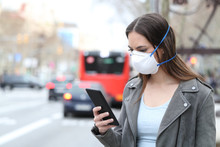 Woman With Mask Using Phone Wi...