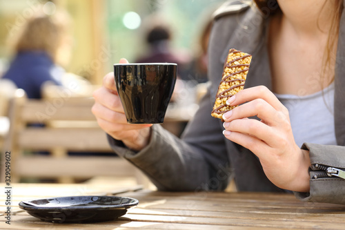 Leinwand Poster Woman holding a snack bar and coffee cup on a terrace