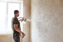 Worker Painting Wall With Spray Gun. Man With A Beard Is Dressed In Paint-smeared Jeans And A T-shirt Against The Background Of A Small Window In The Apartment. Repair Concept