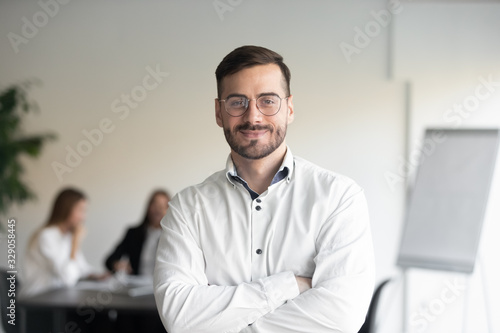 Fotografia Confident happy young male manager in eyeglasses standing with folded hands head shot portrait