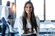 canvas print picture - Smiling young businesswoman looking at camera while standing in the coworking space.