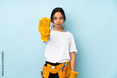 Young electrician woman isolated on blue background making stop gesture Fototapeta