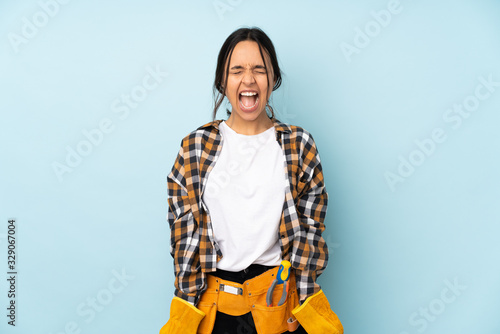 Young electrician woman isolated on blue background shouting to the front with m Wallpaper Mural