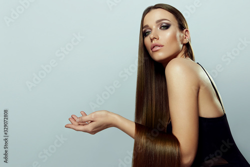 Foto A young, beautiful, well-groomed girl with bright makeup and smooth, silky, long dark hair posing in the studio on a light background