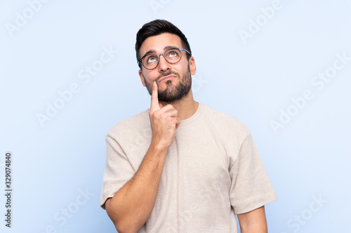 Fototapeta Young handsome man with beard over isolated blue background thinking an idea obraz