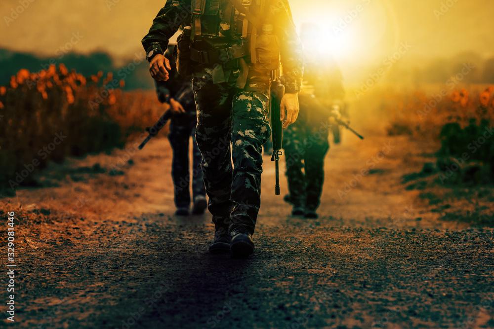 Fototapeta soldier with long rifle gun walking on dirt battle field