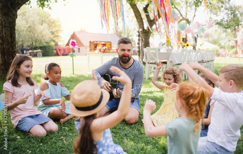 Obraz Man with small children on ground outdoors in garden in summer, playing guitar. - fototapety do salonu