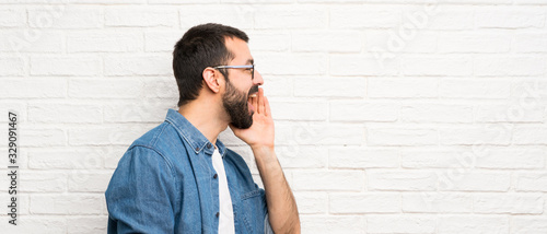 Valokuvatapetti Handsome man with beard over white brick wall shouting with mouth wide open to t