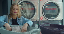 Young Woman Sorting Clothes Fo...