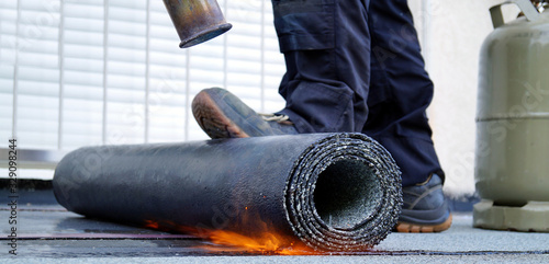 Obraz Heating and melting bitumen roofing felt. Flat roof installation with propane blowtorch during construction works with roofing felt. Roofing felt. Roofer working tool. Waterproofing, panoramic view - fototapety do salonu