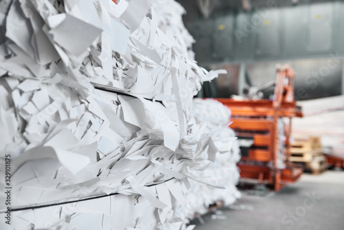 Vászonkép A paper recycling factory plant shredding machine, shredding waste paper into square bails, ready to be pulped and reused