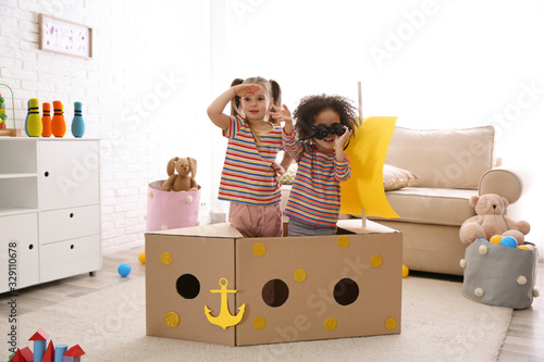 Fototapeta Cute little children playing with cardboard ship and binoculars at home obraz