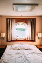 Ship Cabin With Bed And Window With View On Sea. Luxury Cabin On Ferry Boat Or Cruise Liner.