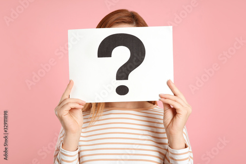 Fotografía Woman holding question mark sign on pink background