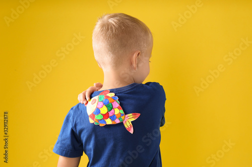 Little boy with paper fish on back against yellow background. April fool's day