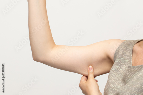 Valokuva Woman pinching the flabby muscle and unwanted excess skin under her arm