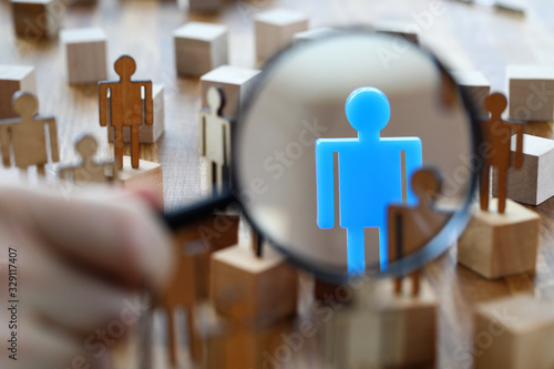 Fototapeta Searching for missing person in crowd of toy human figures with magnifying glass obraz