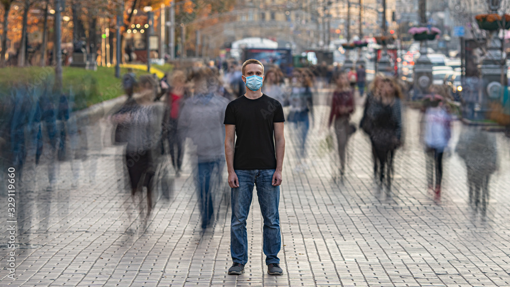 Fototapeta The man with medical face mask stands on the crowded urban street