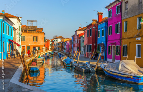 Fototapeta Beautiful view of the canals of Burano with boats and beautiful, colorful buildings. Burano village is famous for its colorful houses. Venice, Italy. obraz