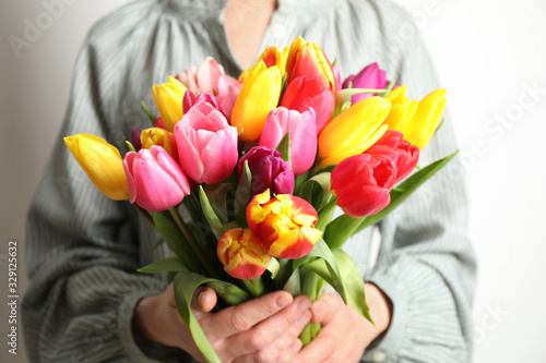 Obraz Woman holding beautiful spring tulips on white background, closeup - fototapety do salonu