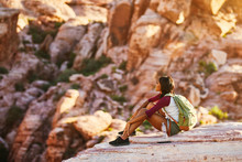 Athletic African American Woman Backpacker On Top Of Tall Cliff At Red Rock Canyon Nevada