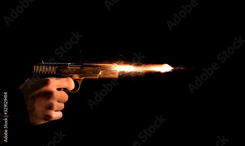 Canvastavla The hand presses the trigger of the gun and the flame from the shot escapes from