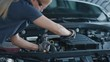 Slow Motion Portrait Footage of a Female Mechanic Working on a Vehicle in a Car Service. Empowering Woman Fixing the Engine. She is Wearing Gloves and Using a Ratchet. Modern Clean Workshop.