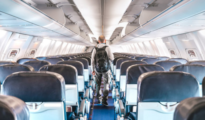 Inside view of commercial airplane with lonely man traveler - Emergency travel concept about flight cancellation - Aerospace industry crisis with empty plane on bright azure filter